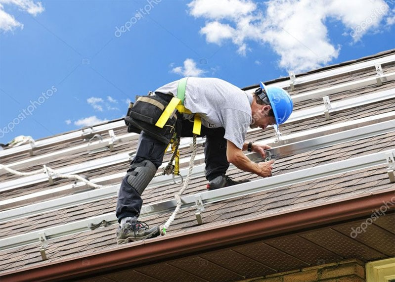 professional roofer in harness on roof