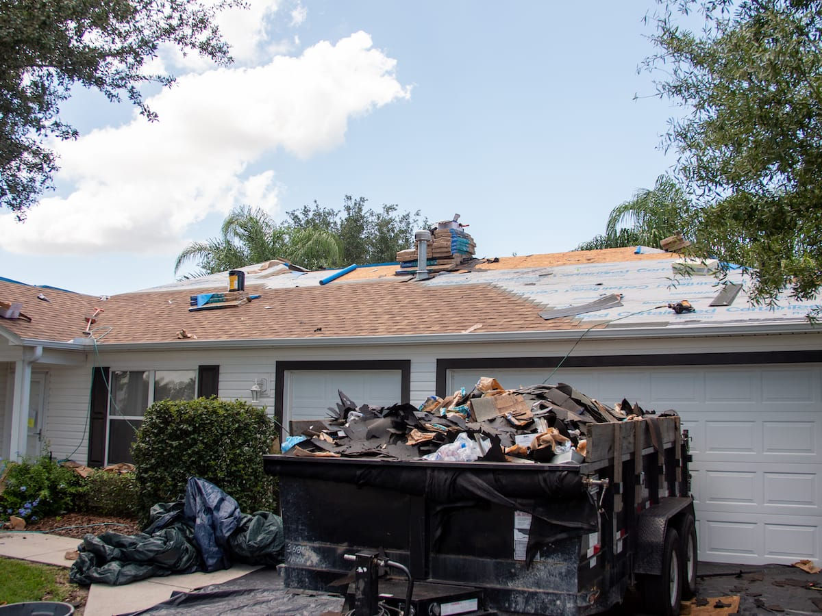 full garbage trailer in front of roof replacement project
