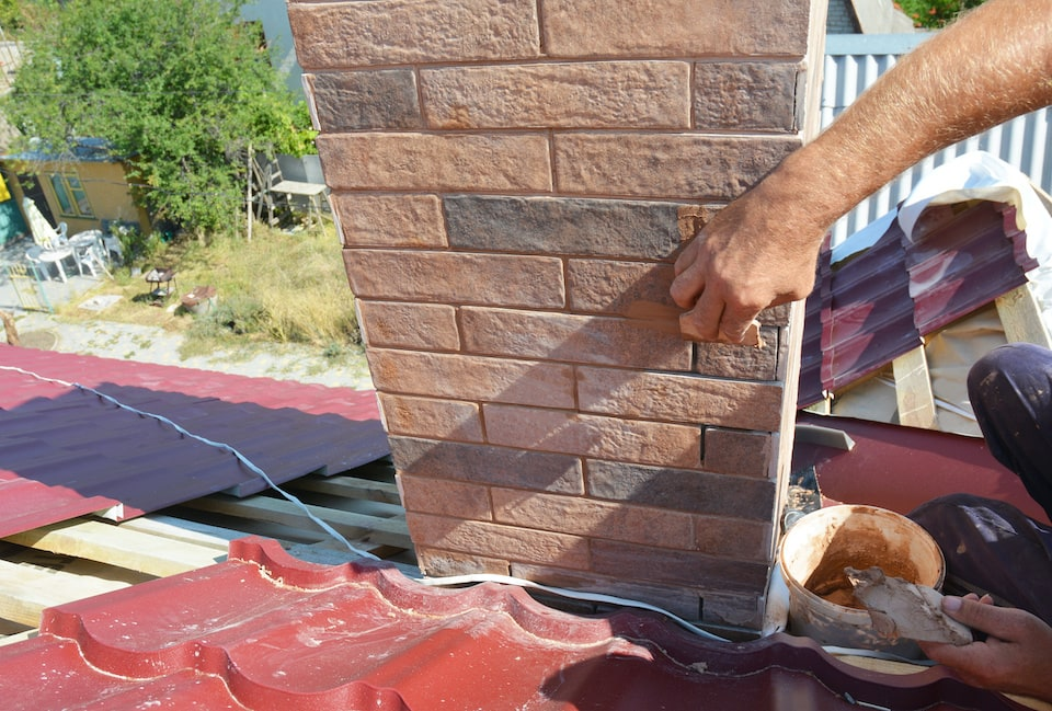 Roofer repair chimney pipe, smoke stake on unfinished house metal roofing construction; roof inspection