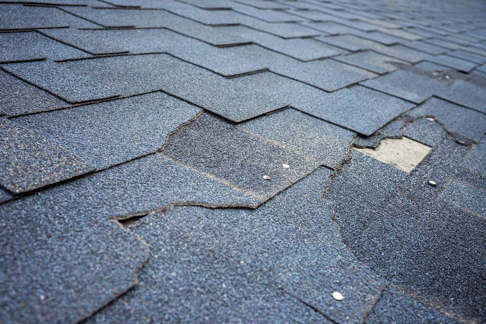 close up view of damaged roof shingles; roof inspection