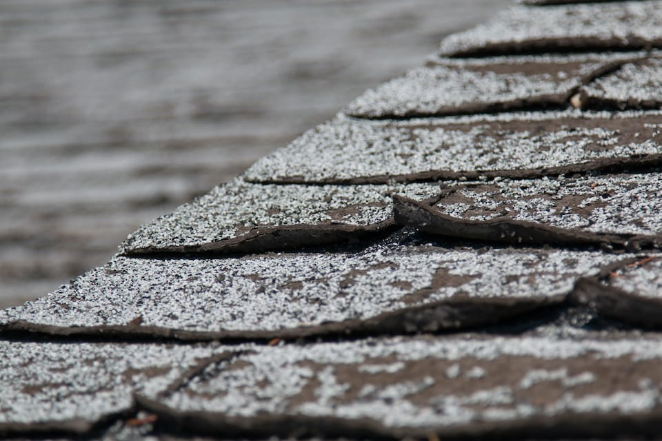 Old worn out asphalt shingles on the roof of a residential home; hail damage roof guide