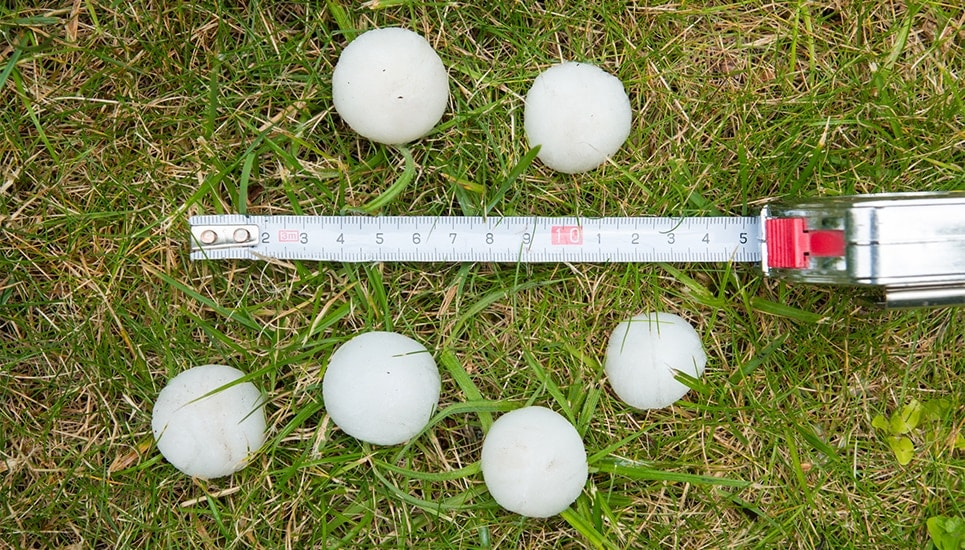 6 large pieces of hail laying on grass next to measuring tape for scale of size; hail damage roof guide