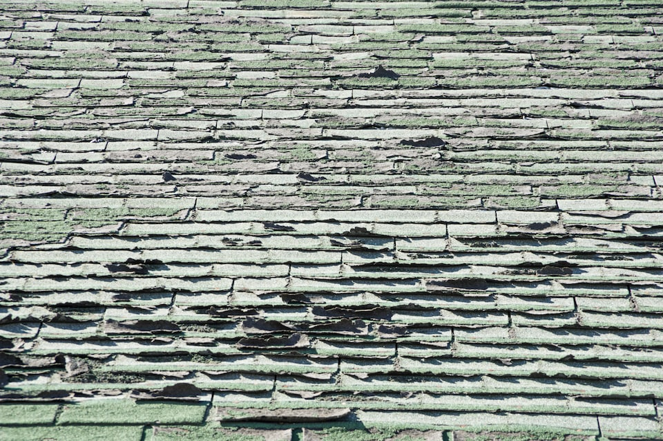 sun damaged old roof with peeling and curling composition shingles; how old is my roof