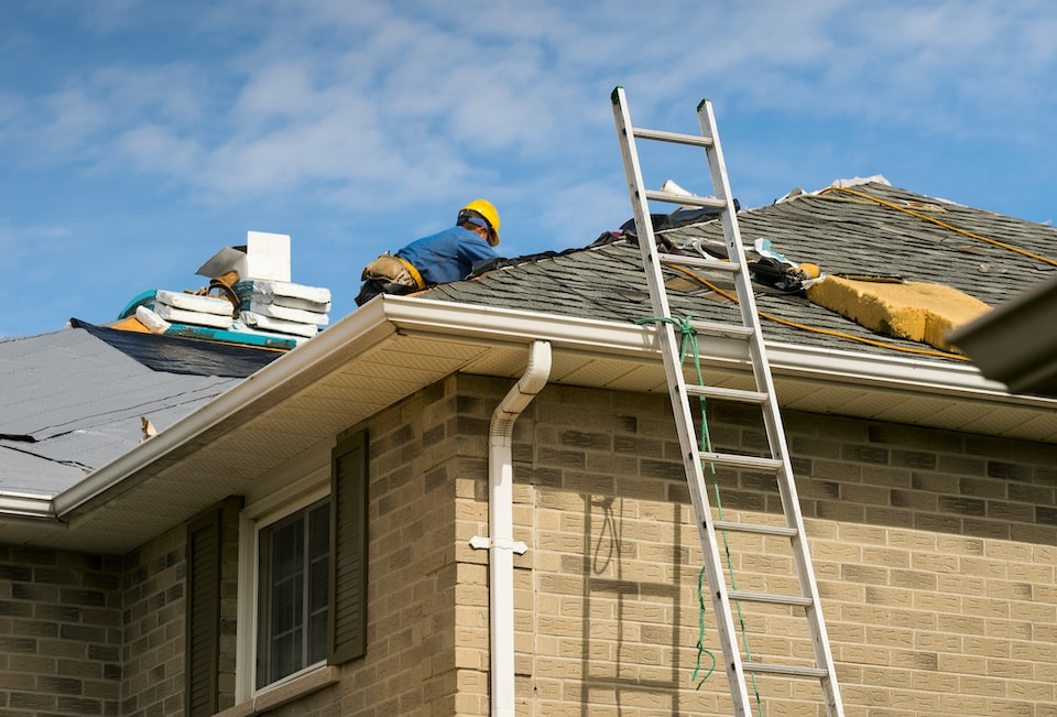 Roof worker installing new shingles on a roof of a house; how long does it take to replace a roof?