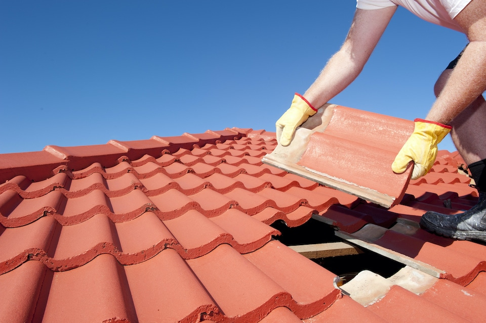 Roof repair, worker with yellow gloves replacing red tiles or shingles on house with blue sky as background and copy space; how long does it take to replace a roof