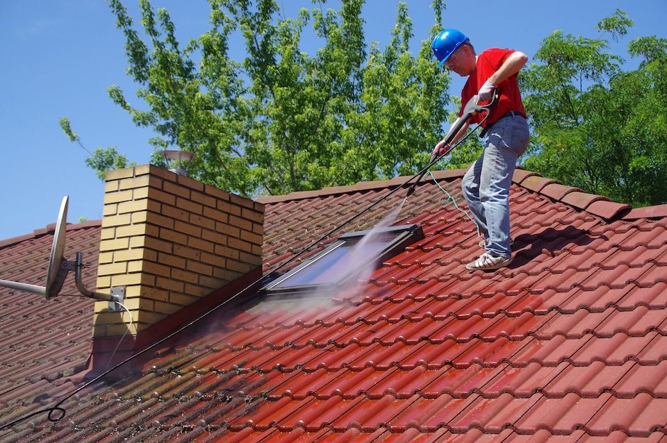 House roof cleaning with pressure tool. Worker on top of building washing tile with professional equipment. Moss removing with water; 8 valuable roof maintenance tips