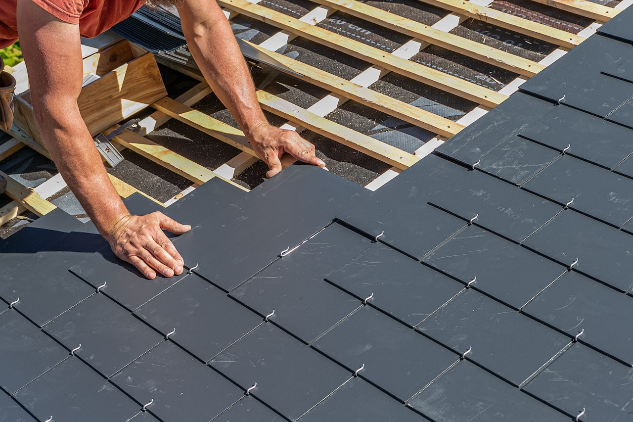 Craftsmen installing a slate roof on a home.