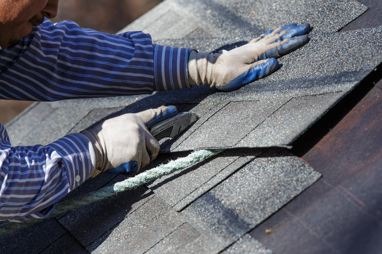 roofer using an utility knife to cut a shingle to fit